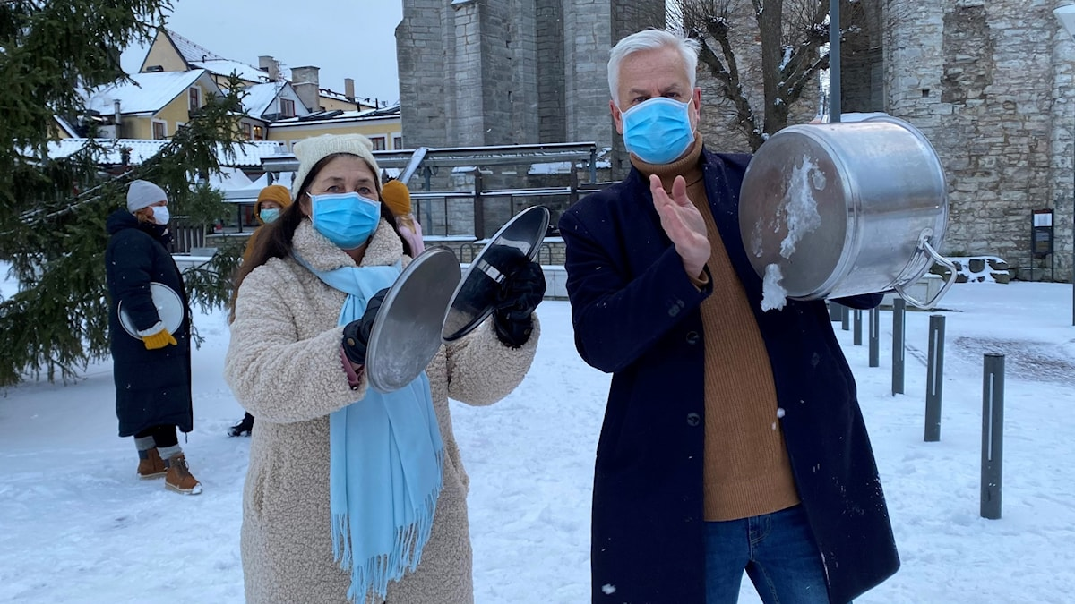 En kvinna och en man har munskydd på sig och står och slamrar med kastruller och lock på Stora Torget i Visby.