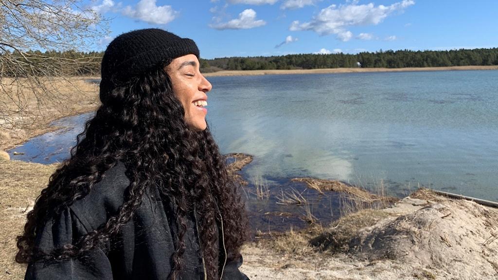 En kvinna i svart jacka, svart mössa och svart hår står framför en sjö och har vänt ansiktet mot solen- Hon ler.