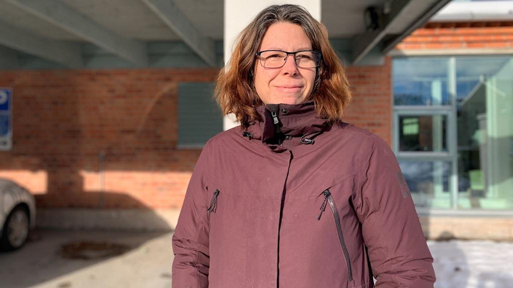 En kvinna med glasögon och vinröd jacka står utomhus.