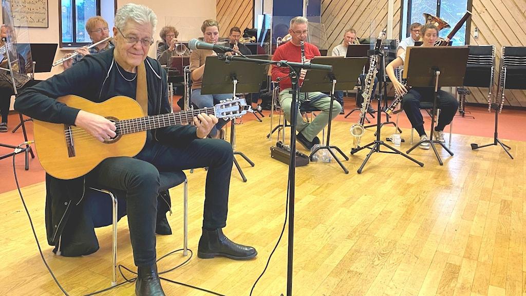 Musikern Jojje Wadenius sitter på en stol och spelar på en akustisk gitar; bakom honom sitter musiker ur Gotlandsmusiken och spelar, bland annat oboe, klarinett och fagott.