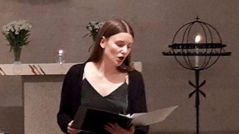 Tilde Rödland sjunger med ett notblad i handen.