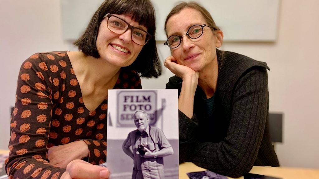 Två kvinnor bredvid varandra, varav den ena håller upp ett foto av en man.