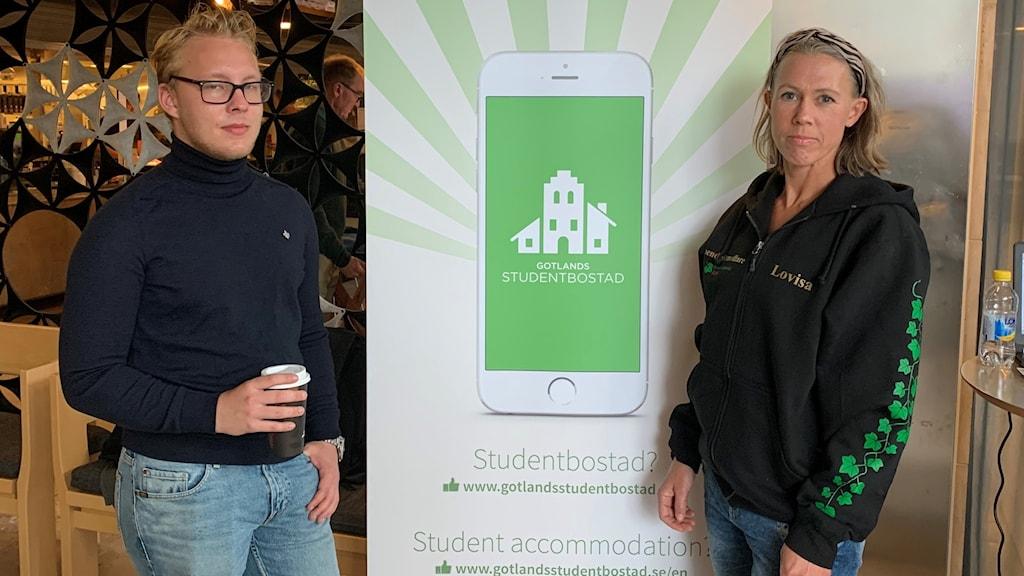 Två personer står framför en roll-up för studentbostäder.