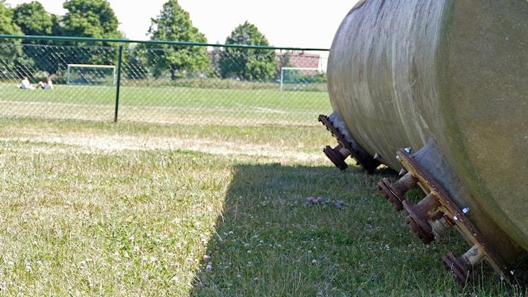 Bild på vattentank som precis dumpats vid en fotbollsplan. På fotbollsplanen sitter tre ungdomar.