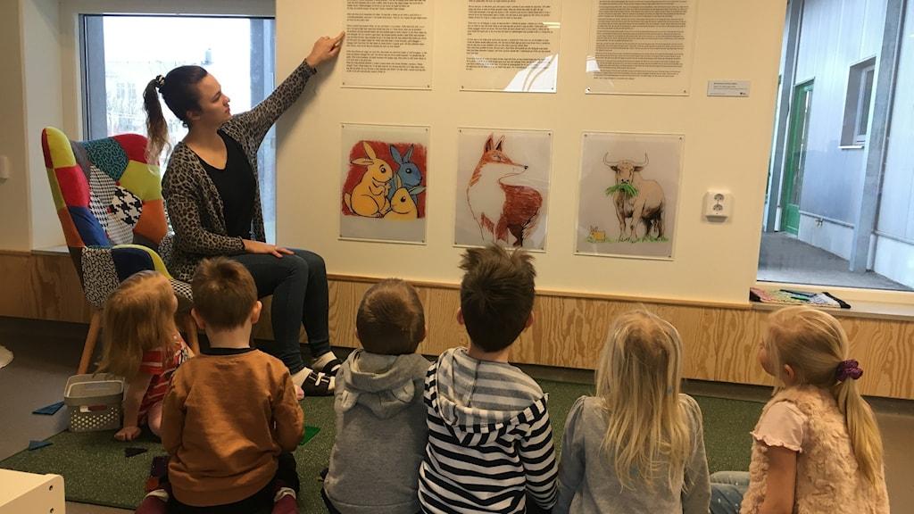 Veronika Löfgren på förskolan Törnekvior i Visby, sitter med en tavla på bilder ur boken. Förskolebarn i förgrunden.