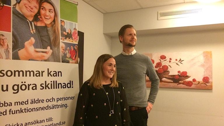 Beatrize Olsson och Roger Nilsson har blickarna riktade åt fjärran, bort från en affisch där det står uppmaningar att söka sig till jobb inom omsorgen.