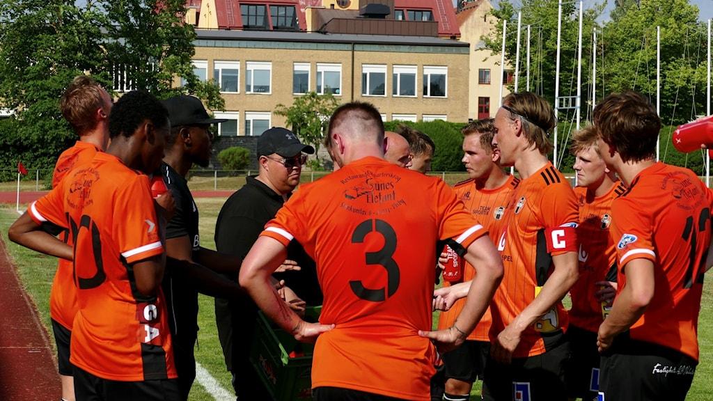 Svettigt fotbollslag i orangea tröjor står med nedböjda huvuden runt tränare och pratar.