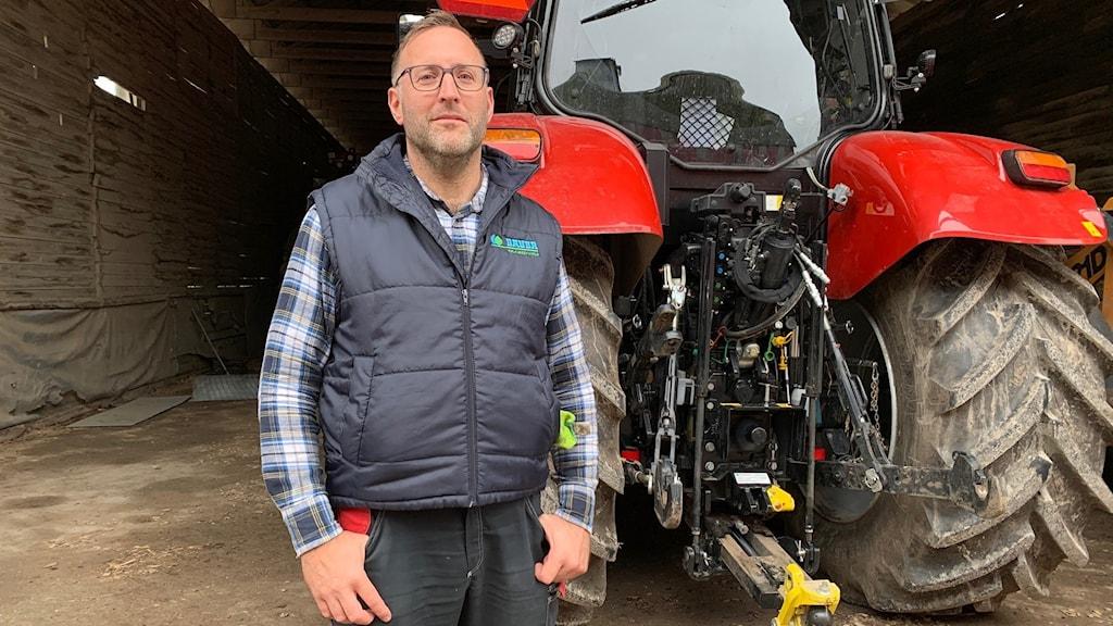 Lantbrukare Svante Runfeldt står framför en traktor på gården i Klinte.