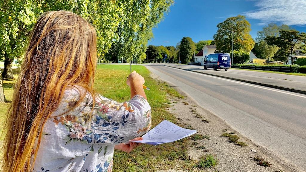 Maria Larsson står vid en bilväg och pekar mot den.