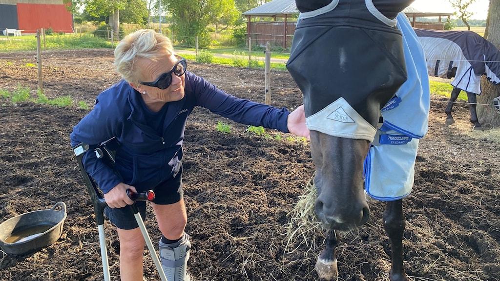 Kvinna med kryckor klappar på häst