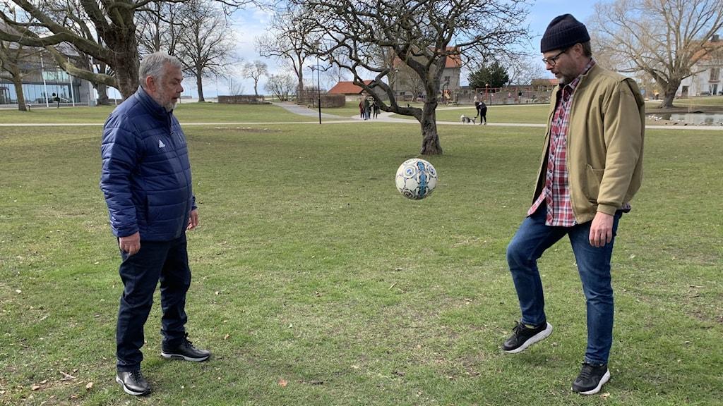 Två män står på en gräsplan och sparkar en fotboll mellan varandra.