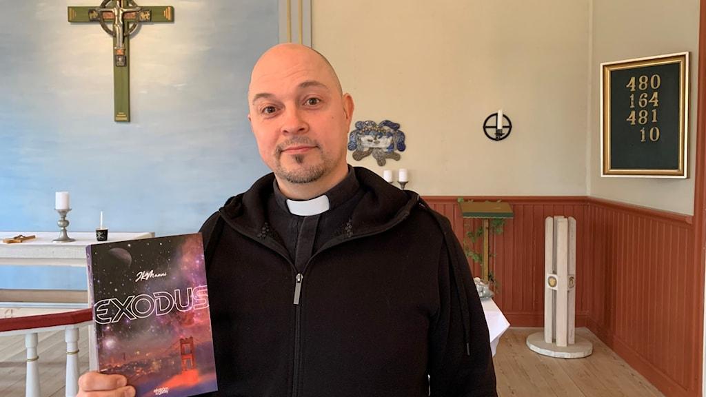 Präst håller stående i kyrka håller upp sciencefictionbok.