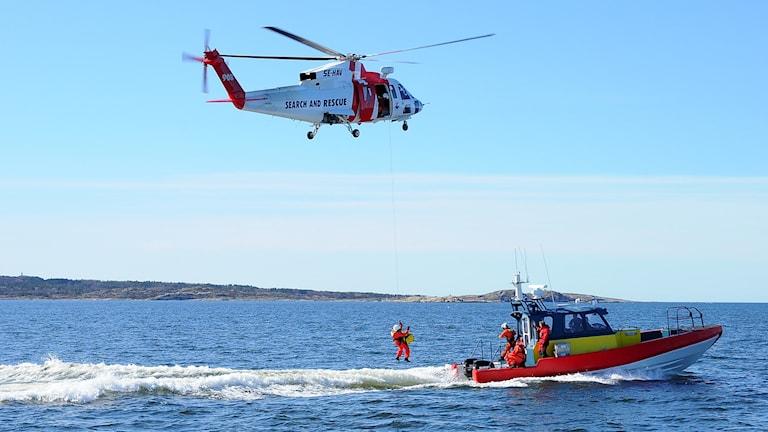 Sjöräddningshelikopter med ytbärgare och båt från sjöräddningssällskapet.