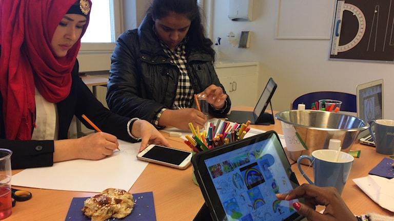 Två unga kvinnor bredvid varandra sitter och ritar på papper, den ena iklädd färgstarkt huvuddok.