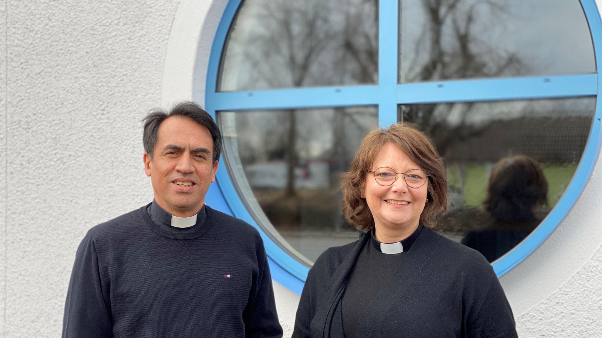 En manlig och en kvinnlig pastor framförrunt fönster