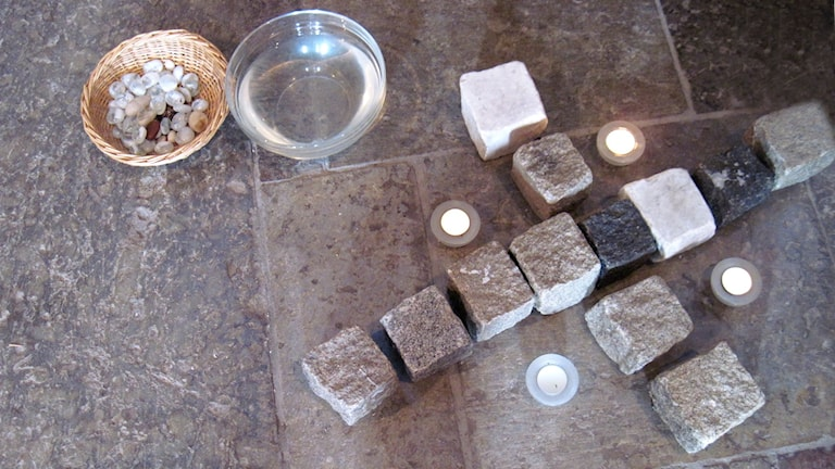 Bönestenar. En sten tas ur korgen, där tänks in allt tungt och jobbigt. Stenen läggs vid korset eller i det renande vattnet. Din sten blir en bön till Gud.  Skara domkyrkas bönestenar.