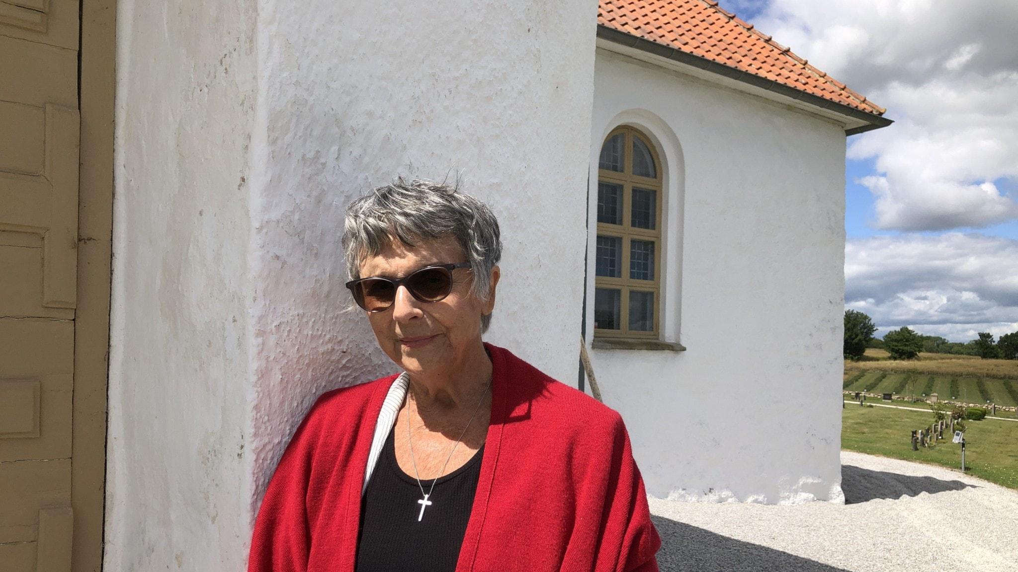 En kvinna i röd schal står vid en kyrkvägg