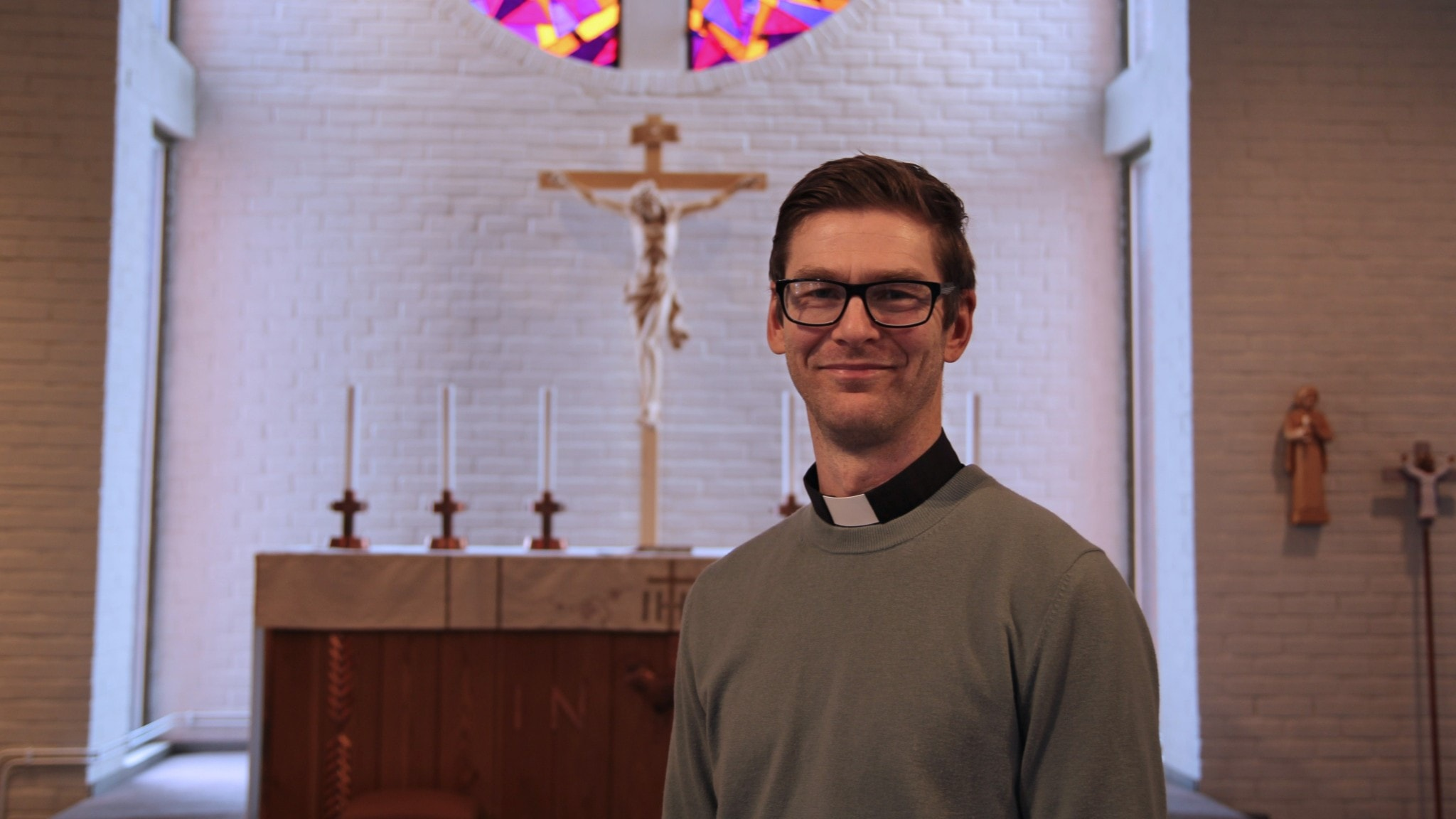 Man i prästskjorta står framför ett altare i en vit tegelkyrka.