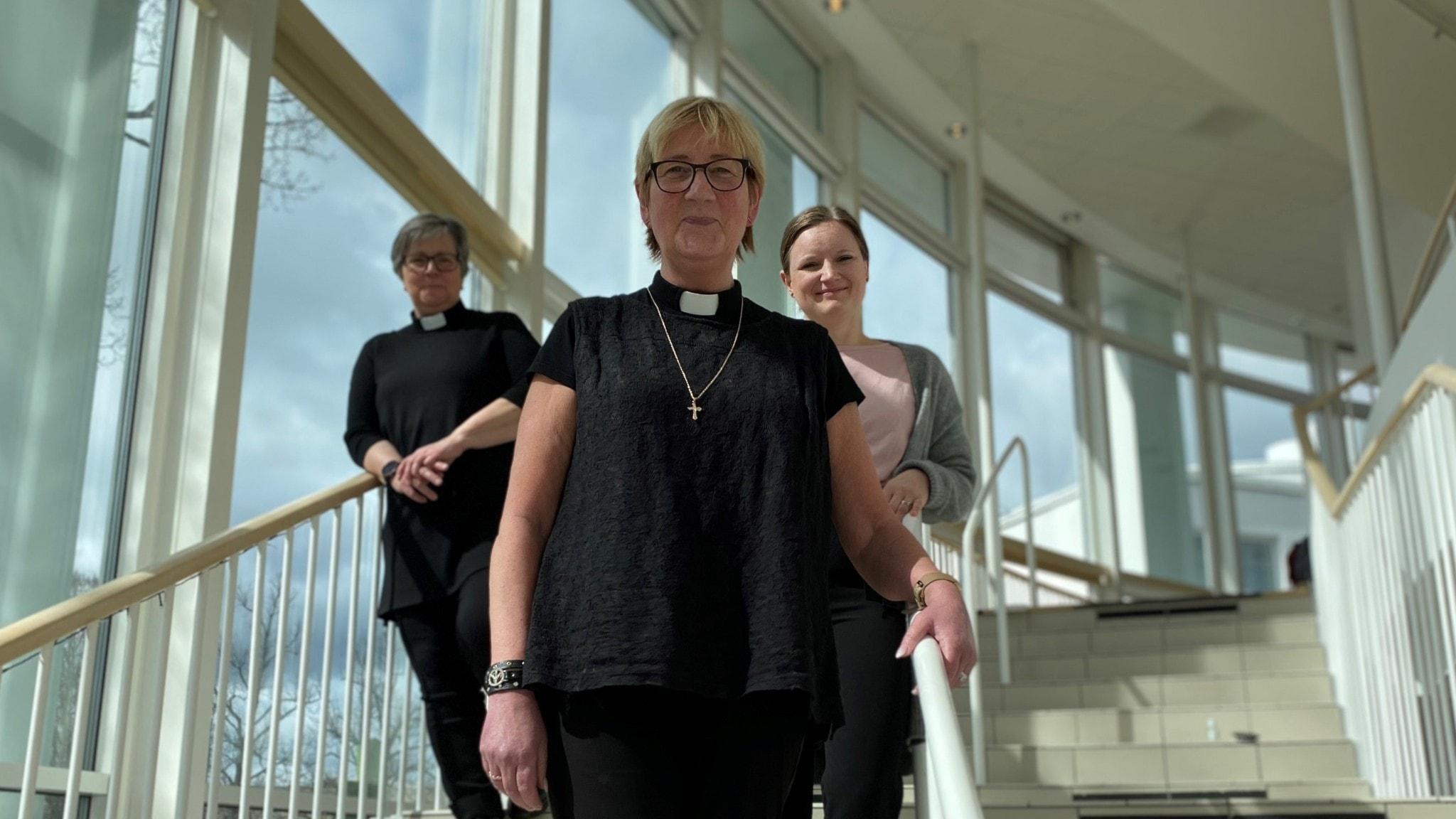 Tre kvinnor i en trappa med fönster bakom