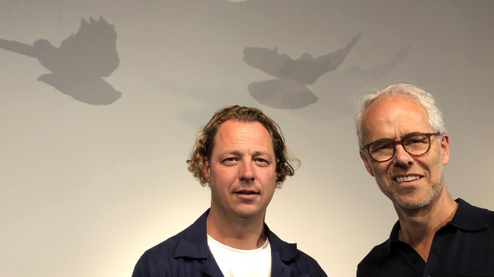 Två män står mot en vit vägg