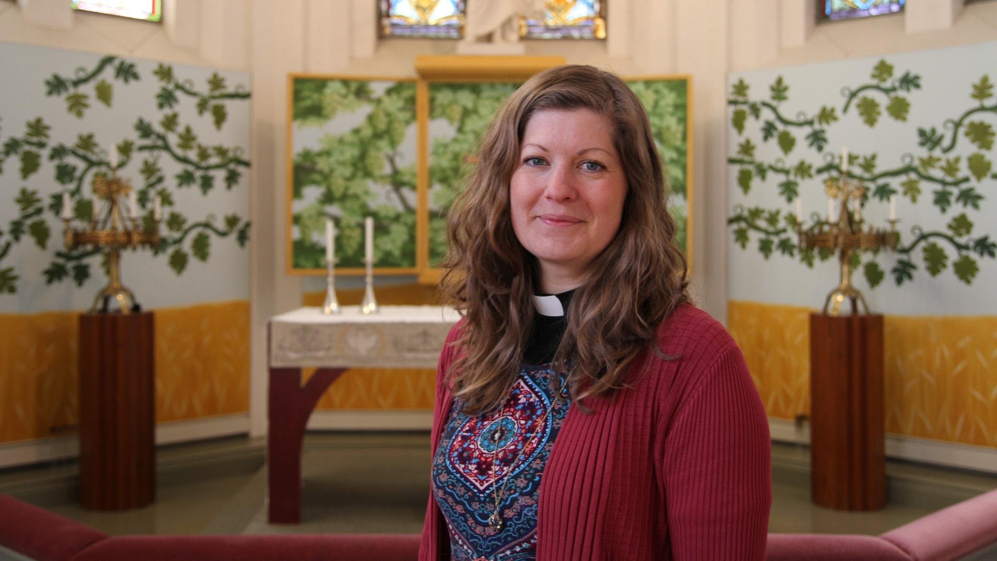 Kvinna i prästskjorta framför en altartavla med grönskande vingrenar.