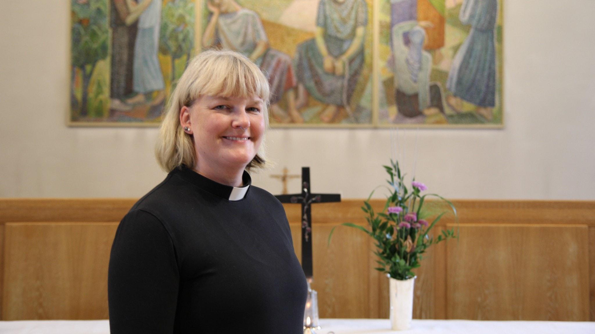 Kvinna i ljus page och svart prästskjorta står framför ett altare.