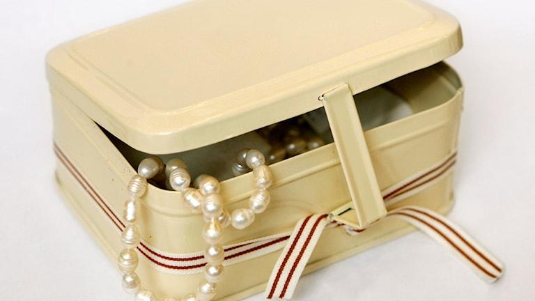 Pärlor hänger ur ett smyckeskrin
