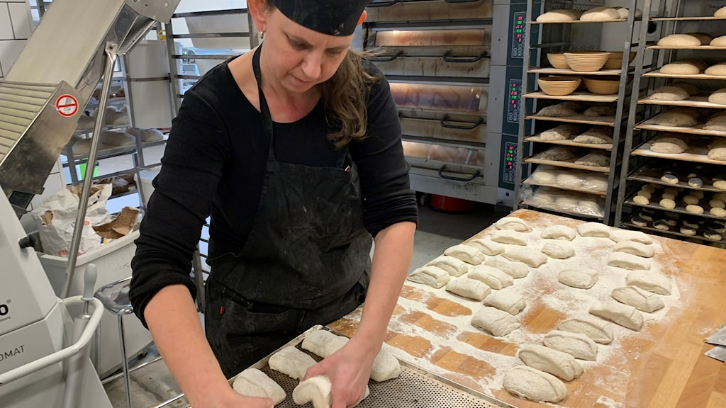 bagare lägger bröd på plåt