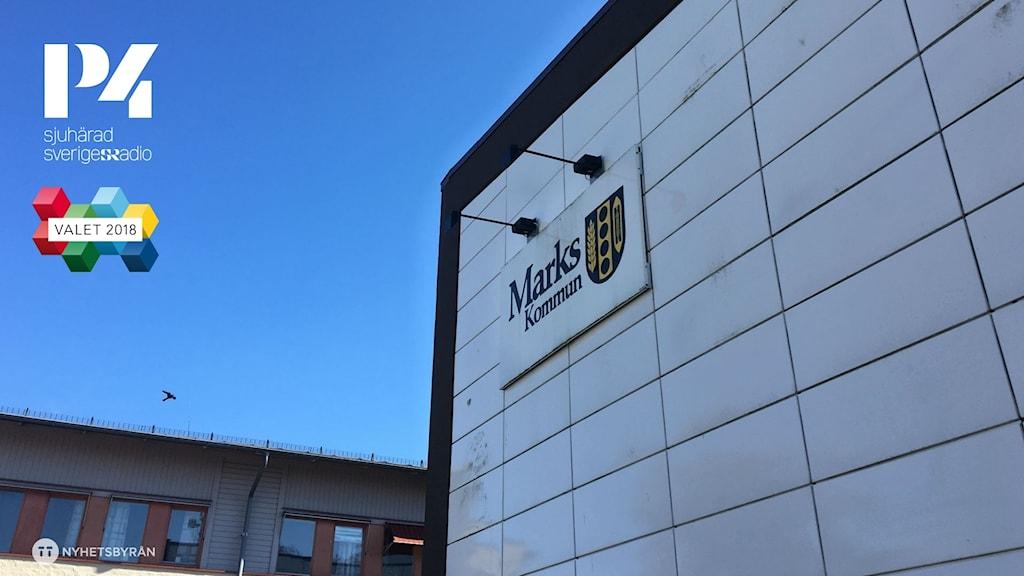 """en vit vägg med en liten skylt med """"Marks kommun"""" i svarta bokstäver, tillsammans med kommunens svart-gula logga. vid sidan syns en klarblå himmel."""