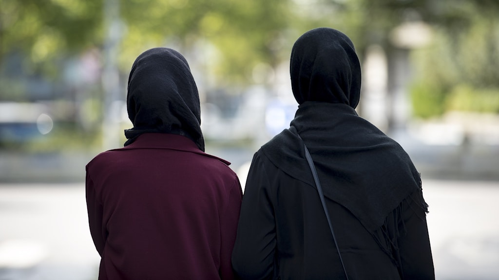 Två kvinnor med hijab står med ryggen emot kameran