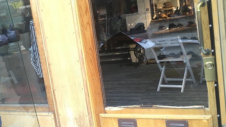 Den sönderslagna glasrutan i entrén till Brissmans klädbutik i Borås.