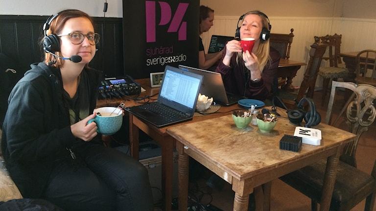 Två kvinnor sitter med var sin kopp på ett cafe