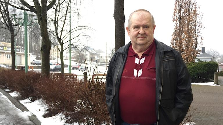 Janåke Sjöqvist står utomhus vid ett snöigt buskage i röd tröja och svart skinnjacka.