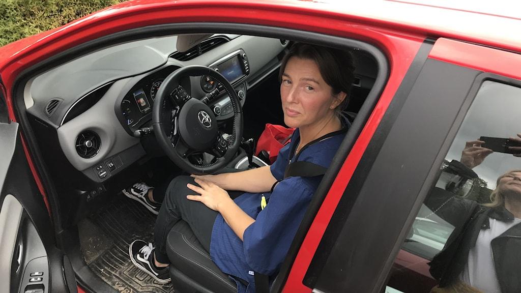 kvinna sitter i bil, bildörren öppen, tittar in i kameran.
