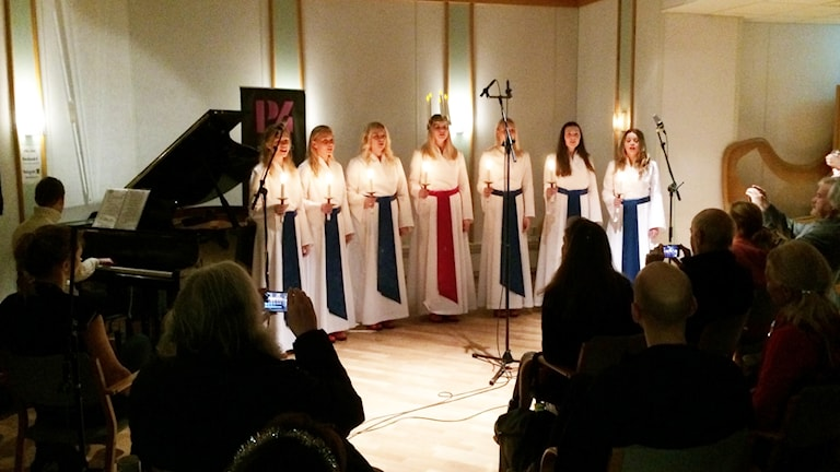 Lucia och tärnor sjunger med ljus i händerna.