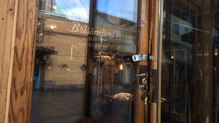 Uppbruten glasdörr med träram med logotypen för klädbutiken Brissmans.