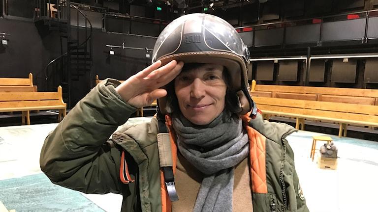 kvinna i mopedhjälm på en teaterscen.