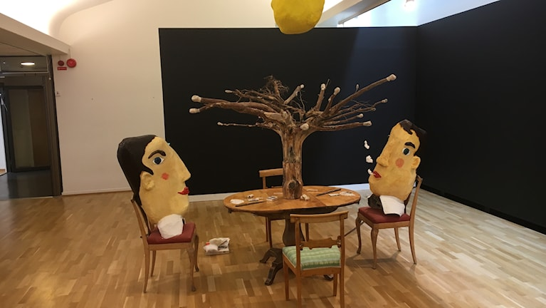 Två dockor i papier maché sitter vid ett bord