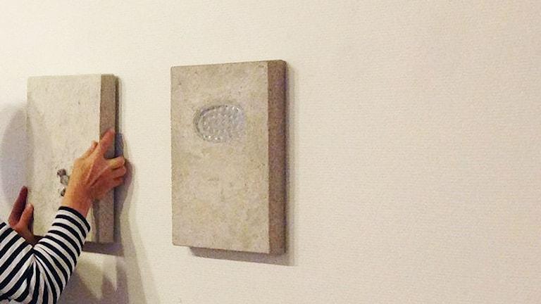 En person hänger upp konstverk på en vägg.