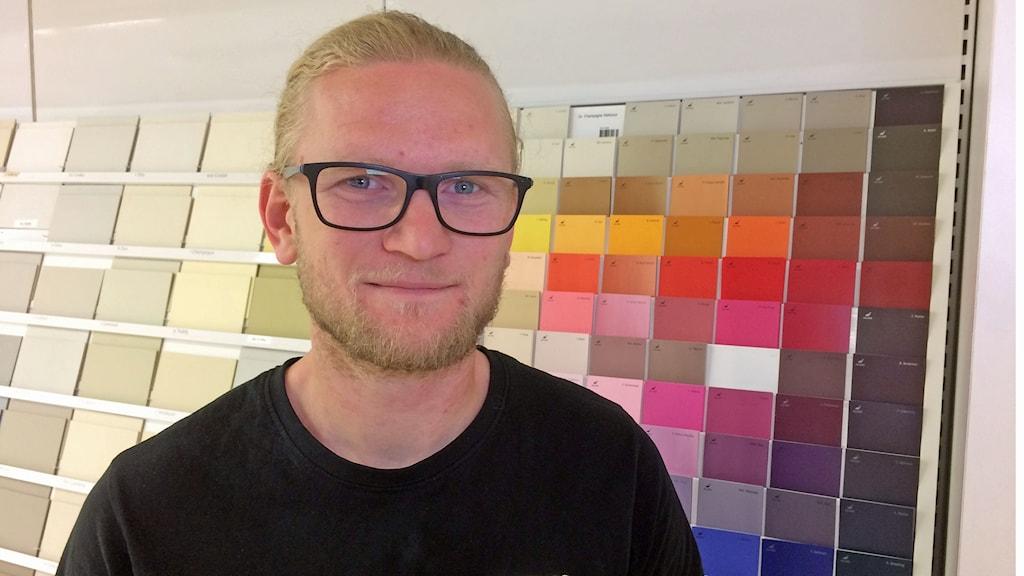 Målaren Andreas Elmelid tittar in i kameran