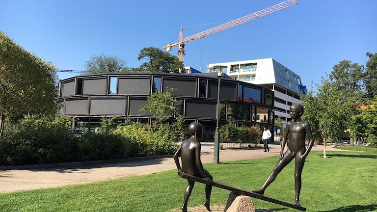 Stadsparken och Orangerietbyggnaden. I förgrunden en skulptur föreställande barn på en gungbräda.