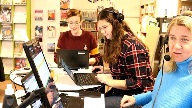Tre kvinnor vid ett skrivbord med datorer och andra teknik