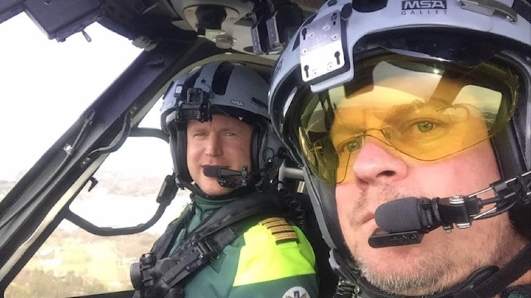 Två män sitter i en helikopter med stora hjälmar och ett orange-färgat ögonskydd.