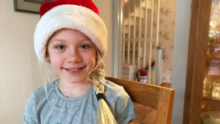 En 9-årig tjej med ljust hår och en tomteluva på huvudet sitter vid ett bord.