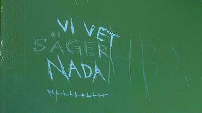 """Inristad text där det står: """"Vi vet säger nada"""" på grön bakgrund (celldörr)"""