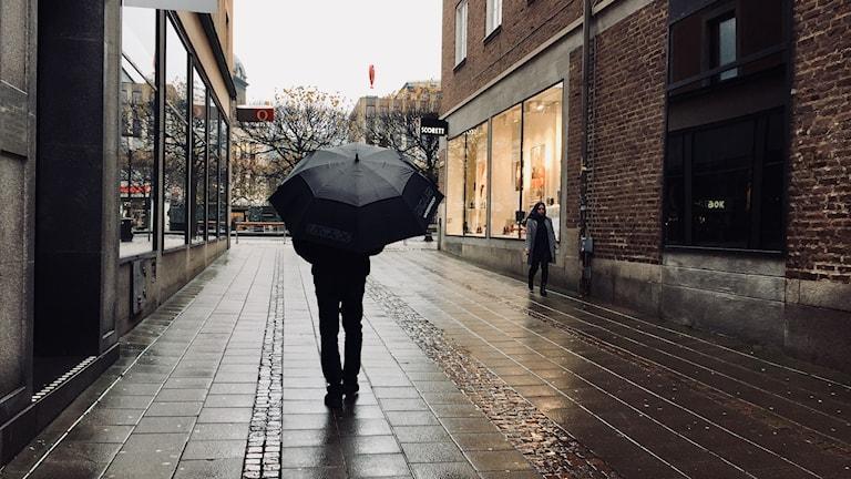 Man går med paraply i centrala Borås.
