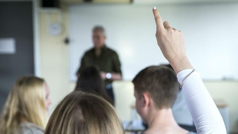 Elev räcker upp handen under en lektion.