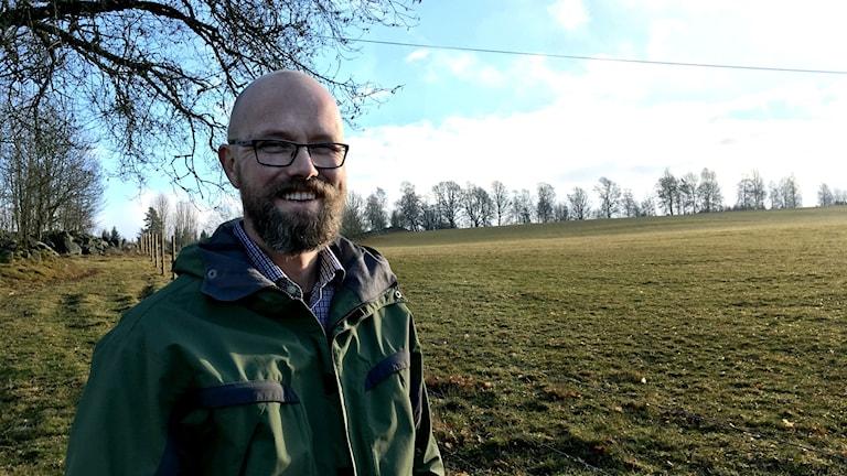 En leende Oskar Lorentzon står till vänster i bild, utomhus, framför en stor åker med grön-gult gräs som breder ut sig mot horisonten. solen skiner och himlen är blå med några vita moln.