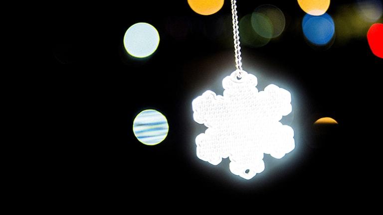 En vit reflex i form av en snöflinga lyser i mörker.