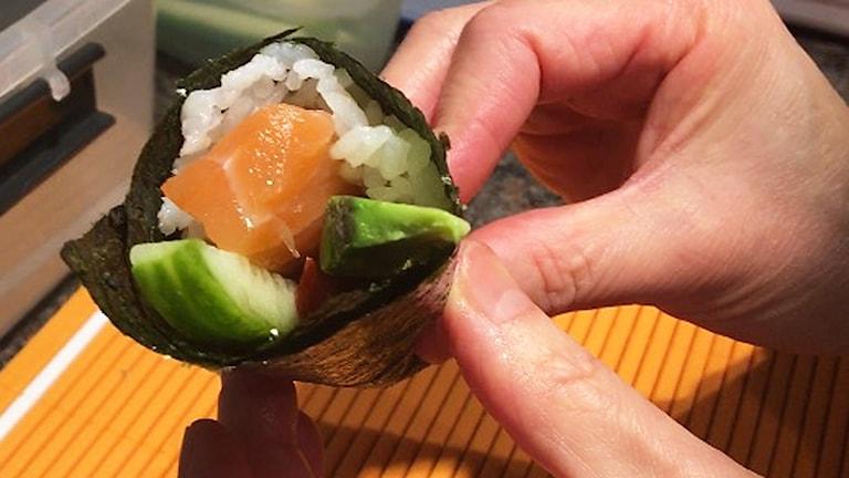 Kocken visar hur man rullar en sushi